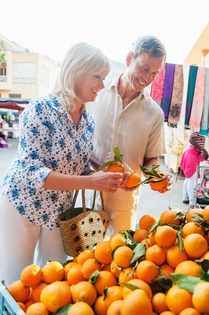 A couple buying oranges at a market, Mallorca, Spain