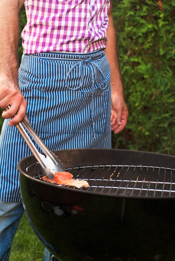 A man wearing an apron grilling salmon trout fillet in a garden