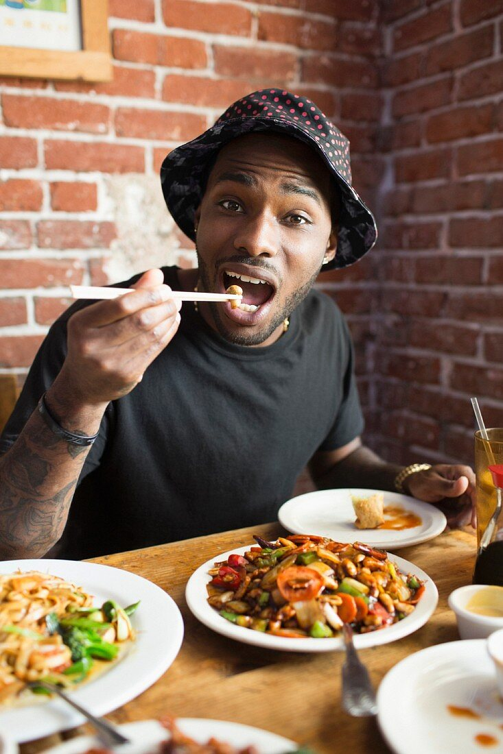 An African American man eating in a restaurant