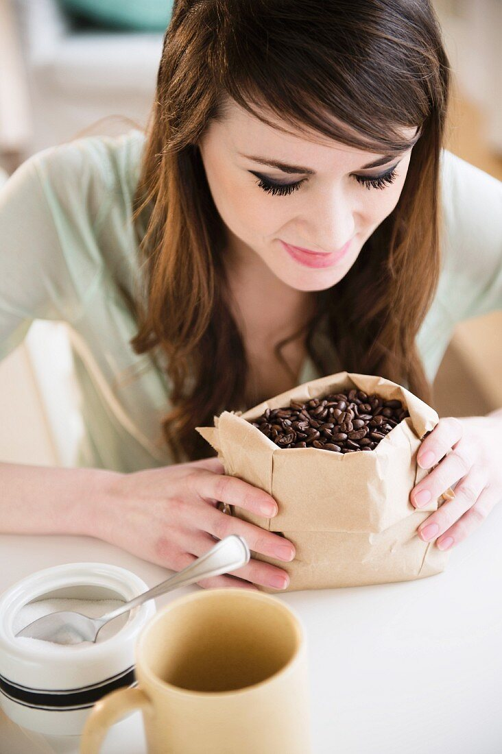 A young woman looking at a sack of coffee beans
