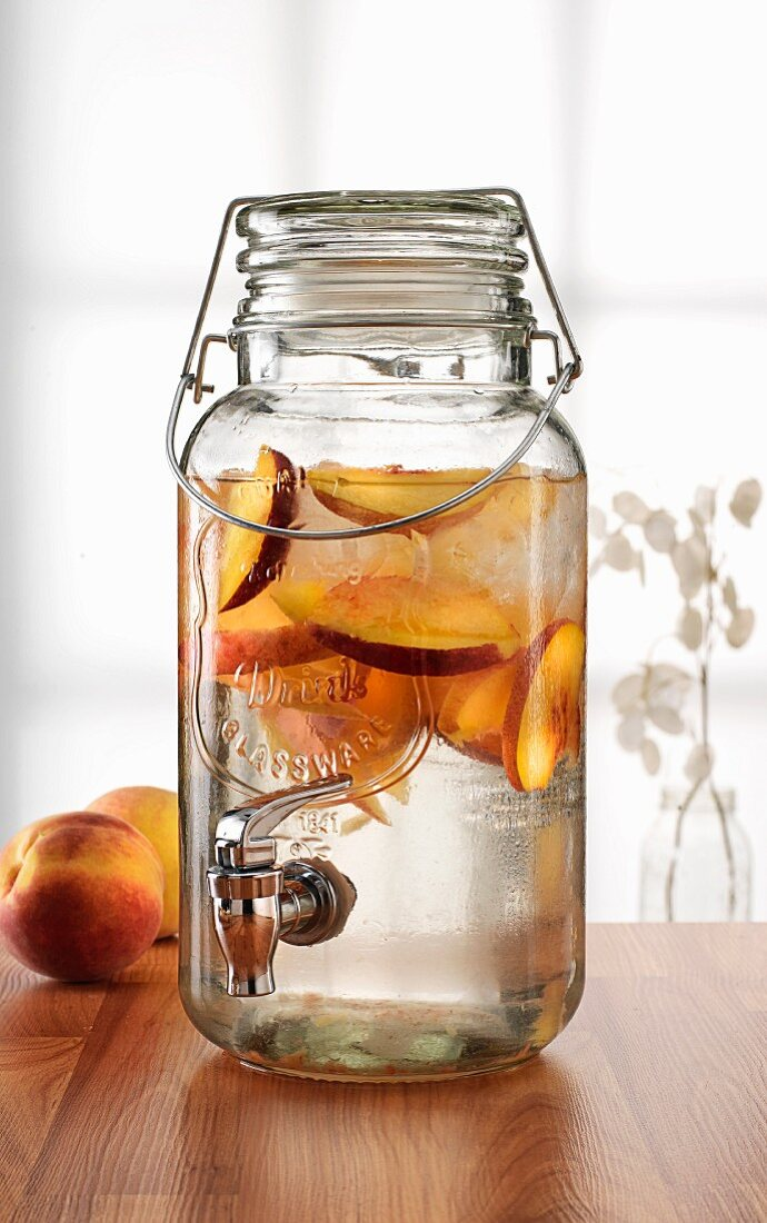 Peach drink in a jar with a tap