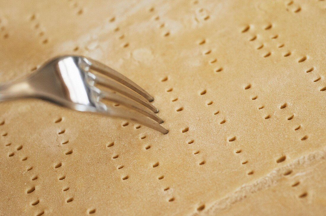 Shortcrust pastry base being pierced with a fork