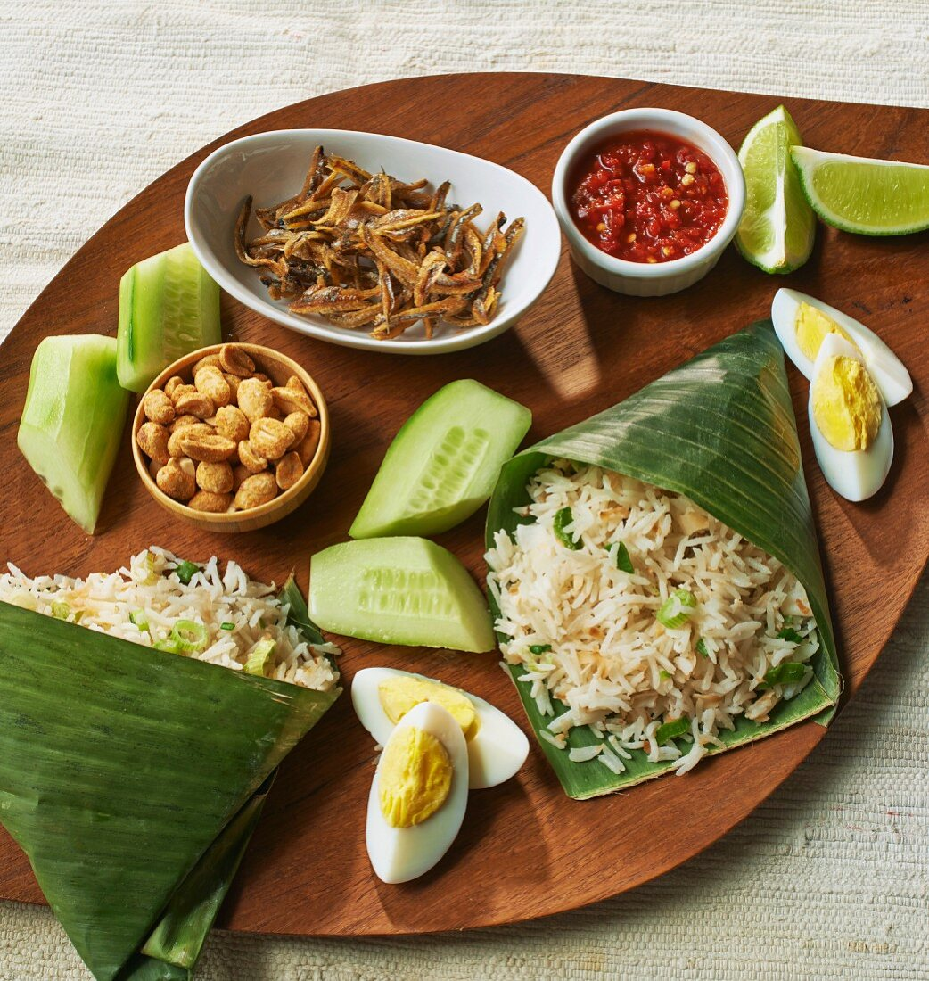 Coconut rice in banana leaves, eggs, fish, cucumber and dip (Asia)