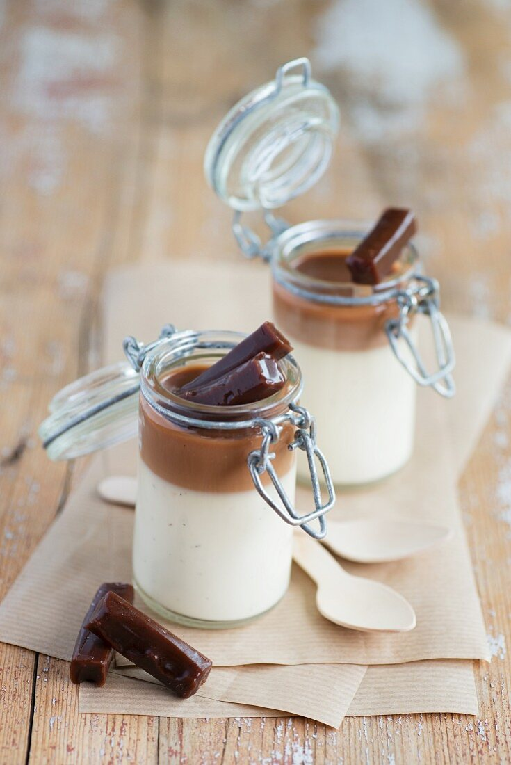 Panna cotta with a layer of caramel served in small flip-top jars