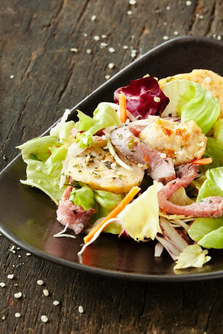 A salad with sliced bread dumplings and roast beef