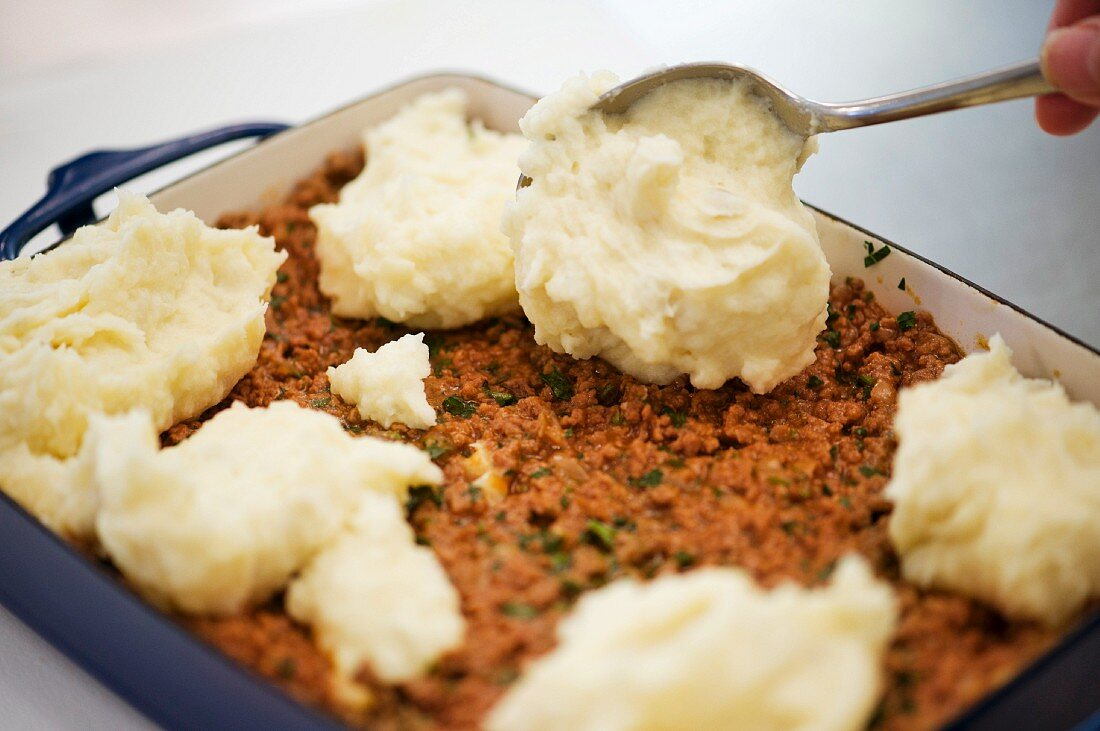 Mashed potatoes being added to a minced meat bake