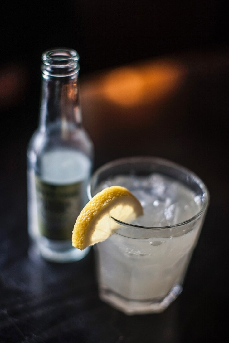 A drink with ice and a slice of lemon
