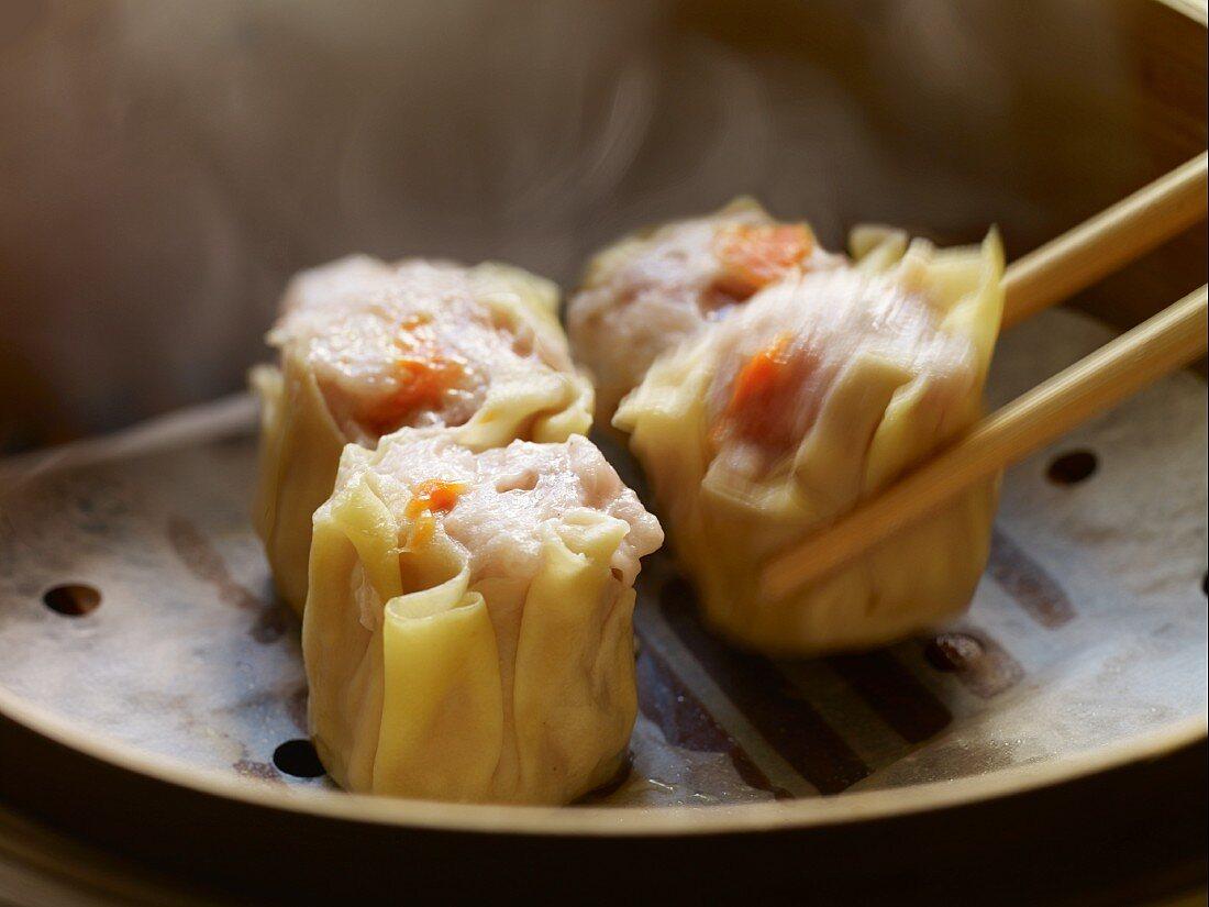 Siu Mai Dim Sum (Cantonese pork and prawn dumplings) one being lifted with chop sticks