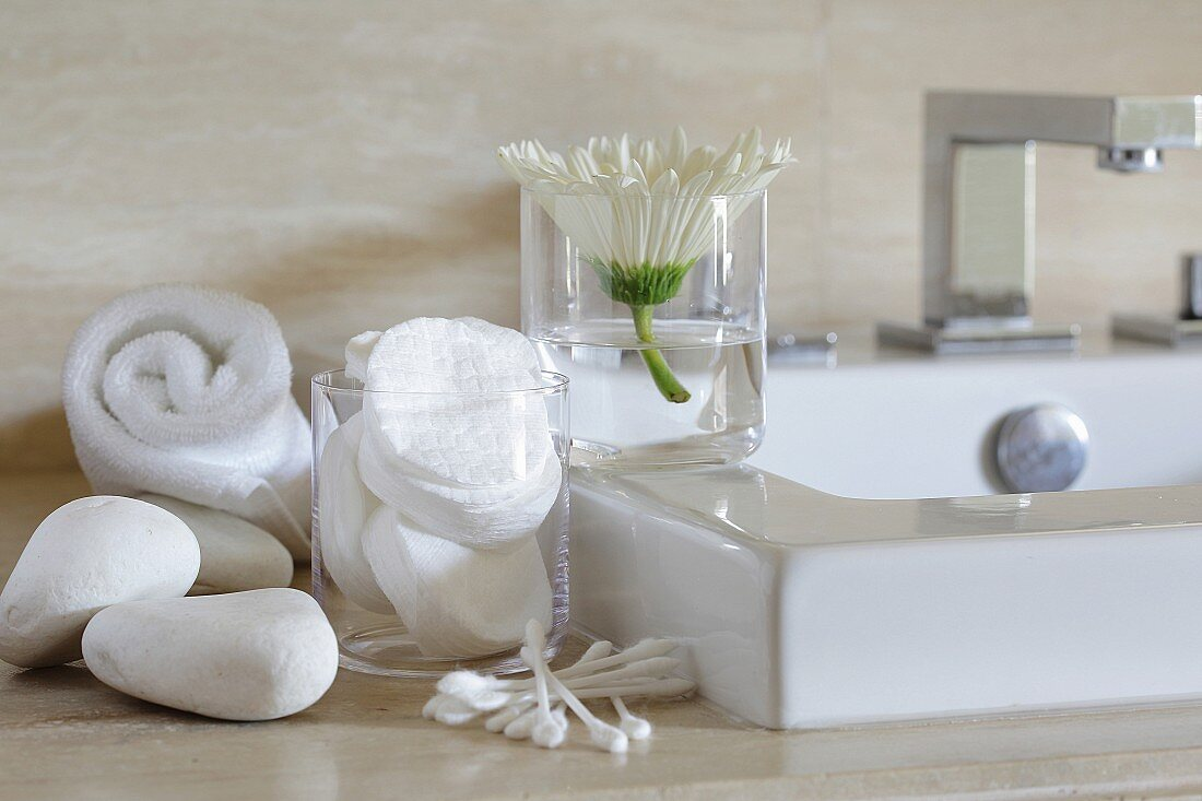 Various cosmetic items next to a wash basin in a bathroom