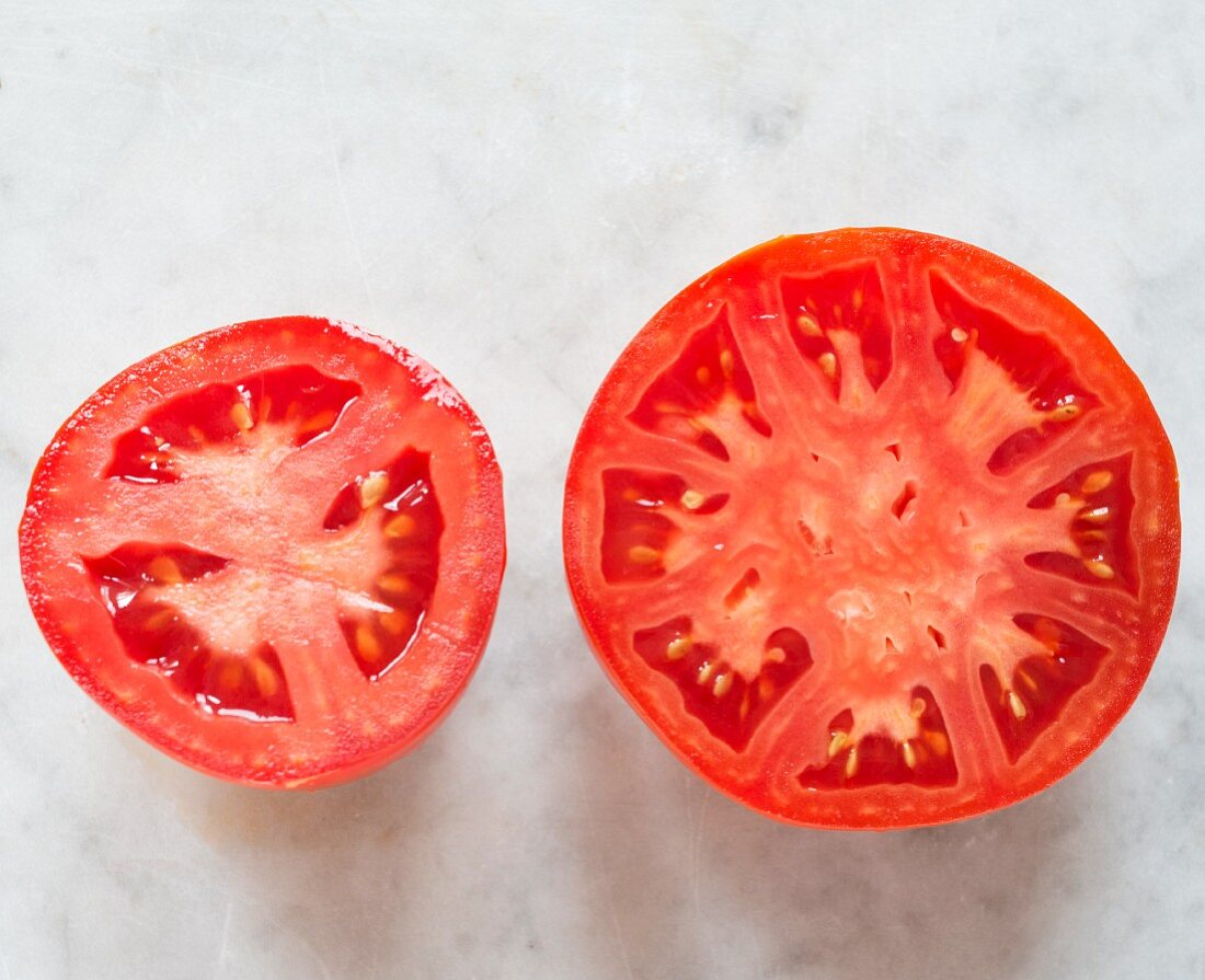 Two tomatoes halves of different sizes