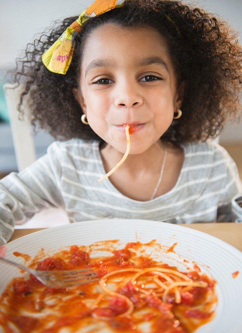 An African American girl eating spaghetti