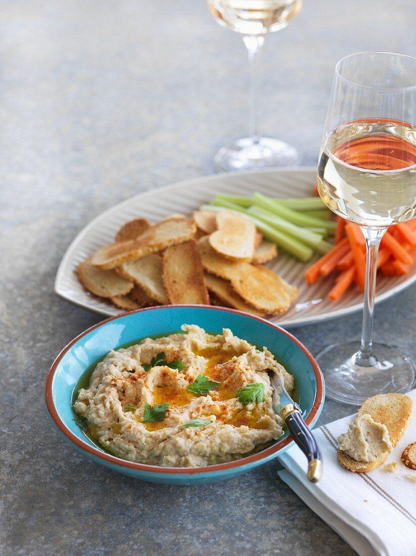 Artichoke dip with vegetable sticks, crostini and wine
