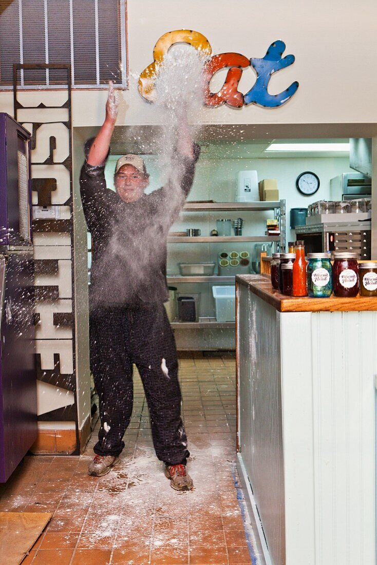 A chef in a restaurant throwing flour in the air