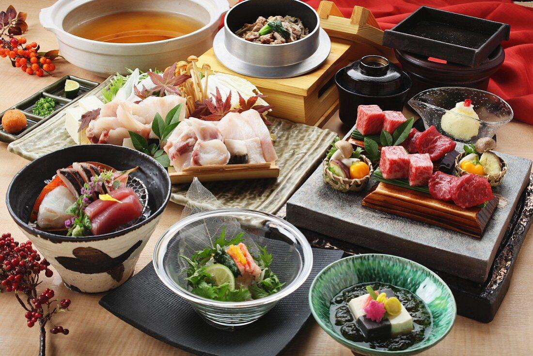 Traditional Japanese dishes: beef, chicken, tofu, sashimi and salad
