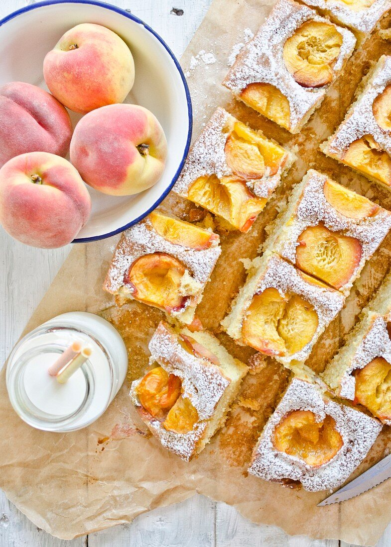 Peach cake with icing sugar, sliced