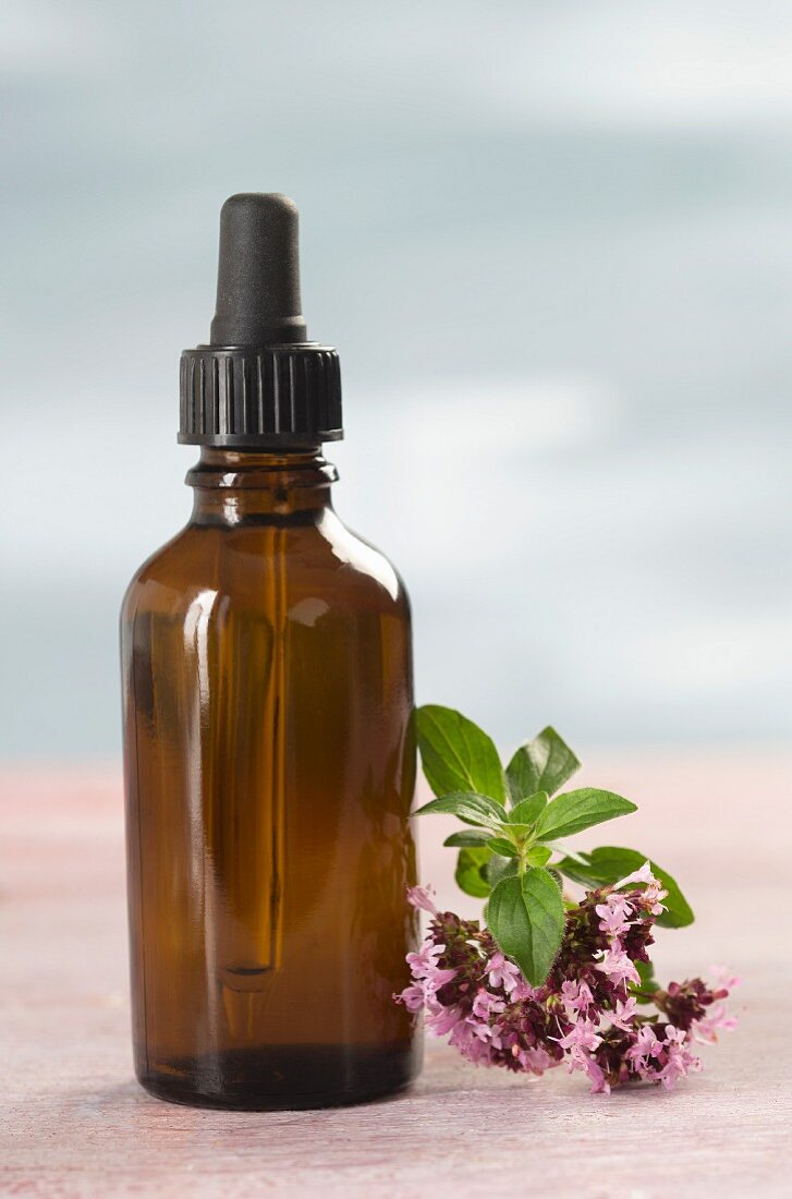 A dropper bottle and oregano flowers