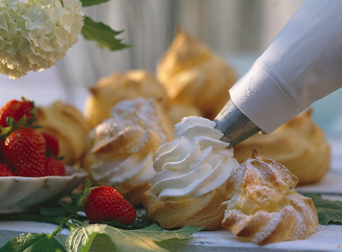 Filling cream puffs with whipped cream using a piping bag