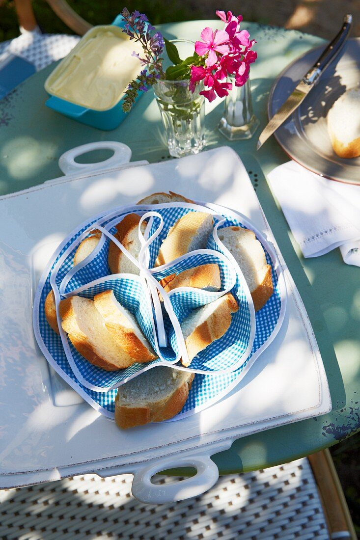 A partitioned bread basket for baguette slices and a serving platter on a breakfast table in a garden