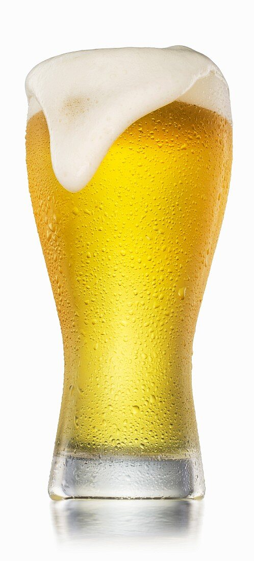 A full glass of beer with water droplets and a head spilling over