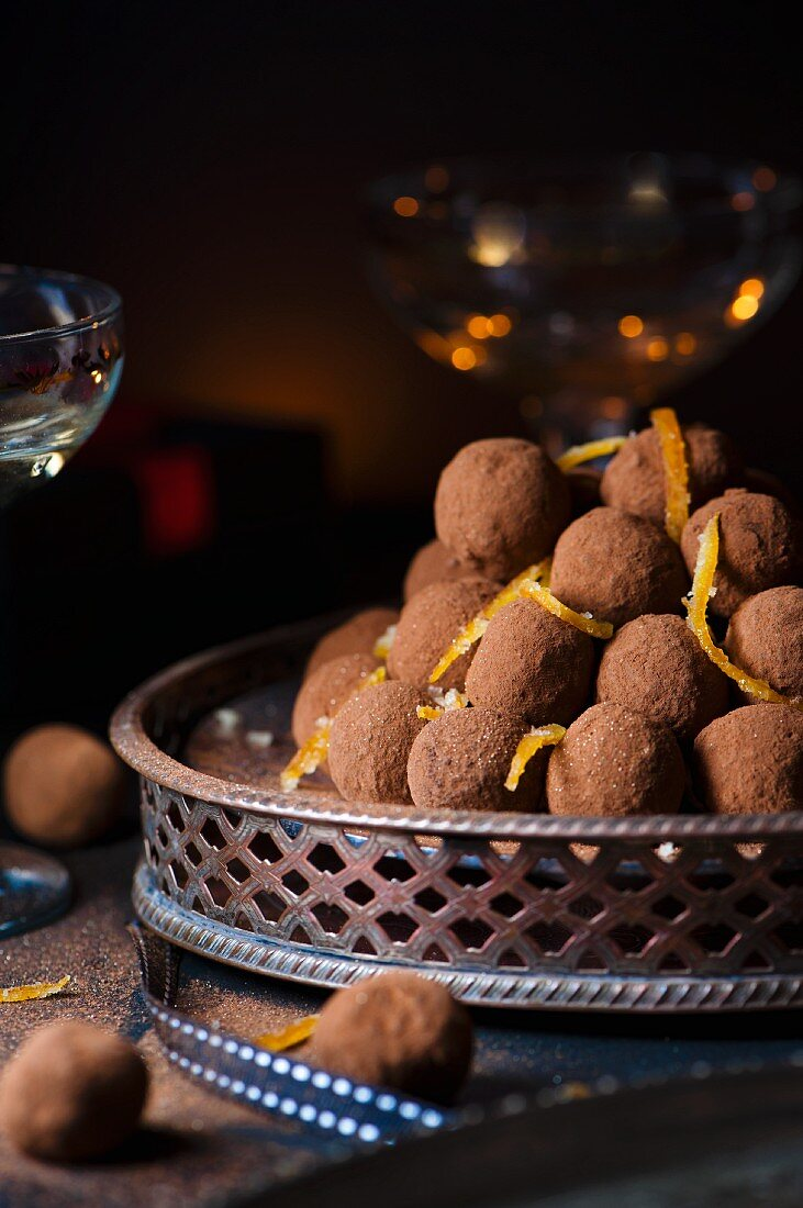 A pile of dark chocolate truffles with cocoa powder and orange zest