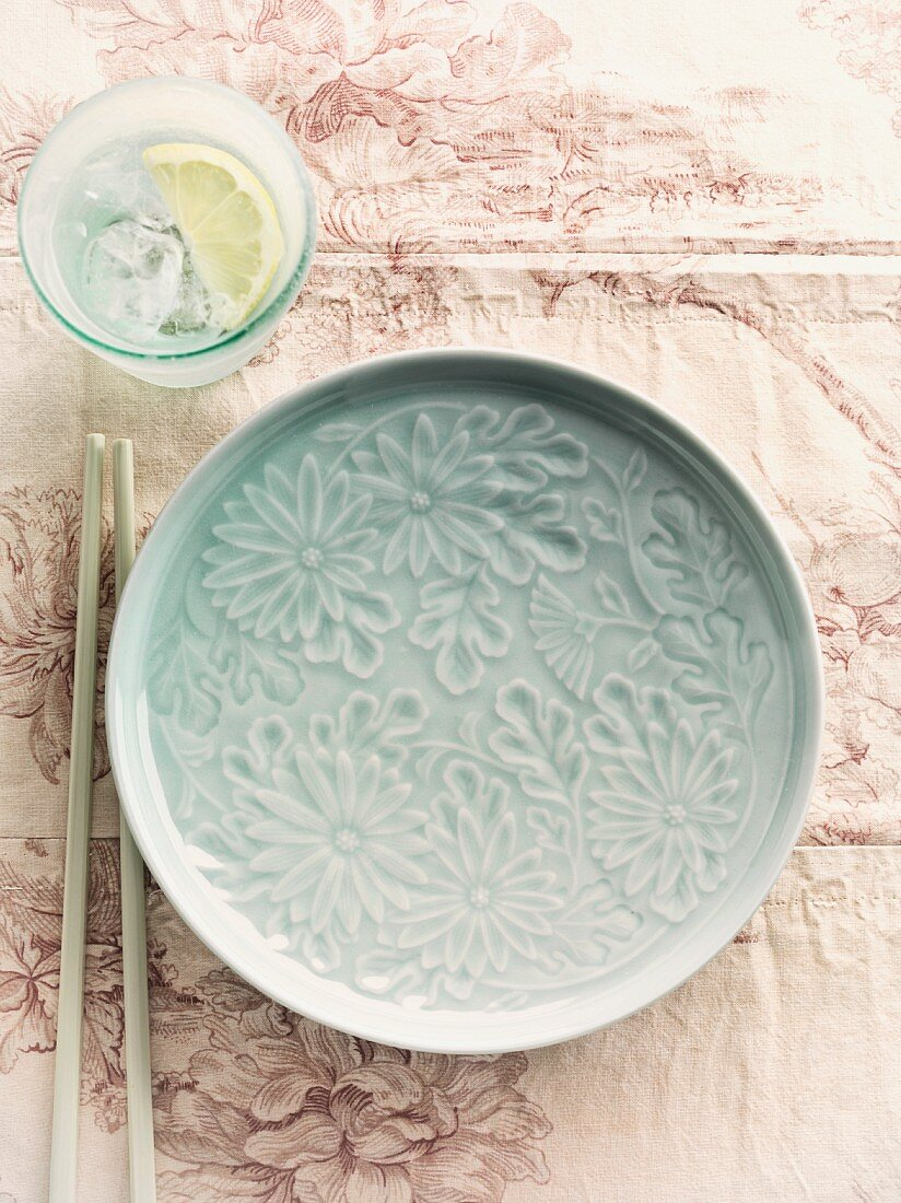 A floral patterned plate, chopsticks and lemon water (China)