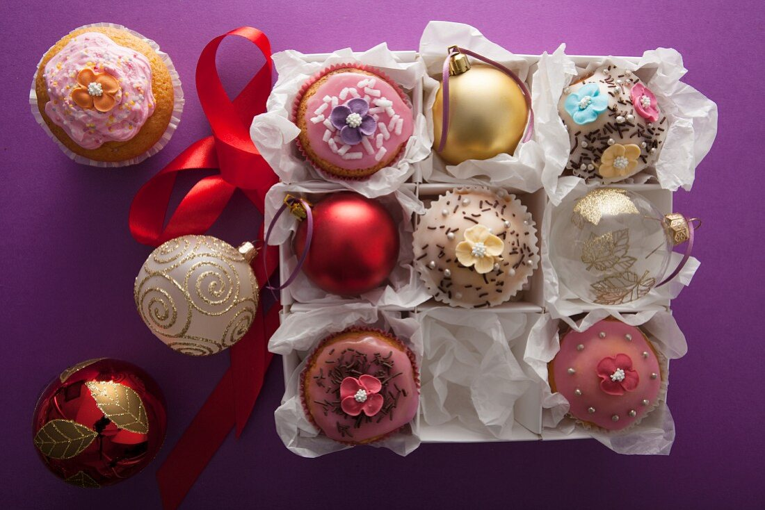 Christmas cupcakes and petit fours between Christmas baubles