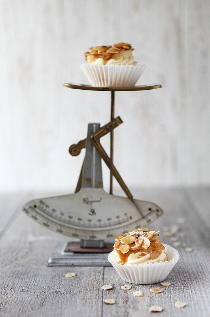 Bienenstich muffin (caramelised almond cake) on and in front of an old pair of scales