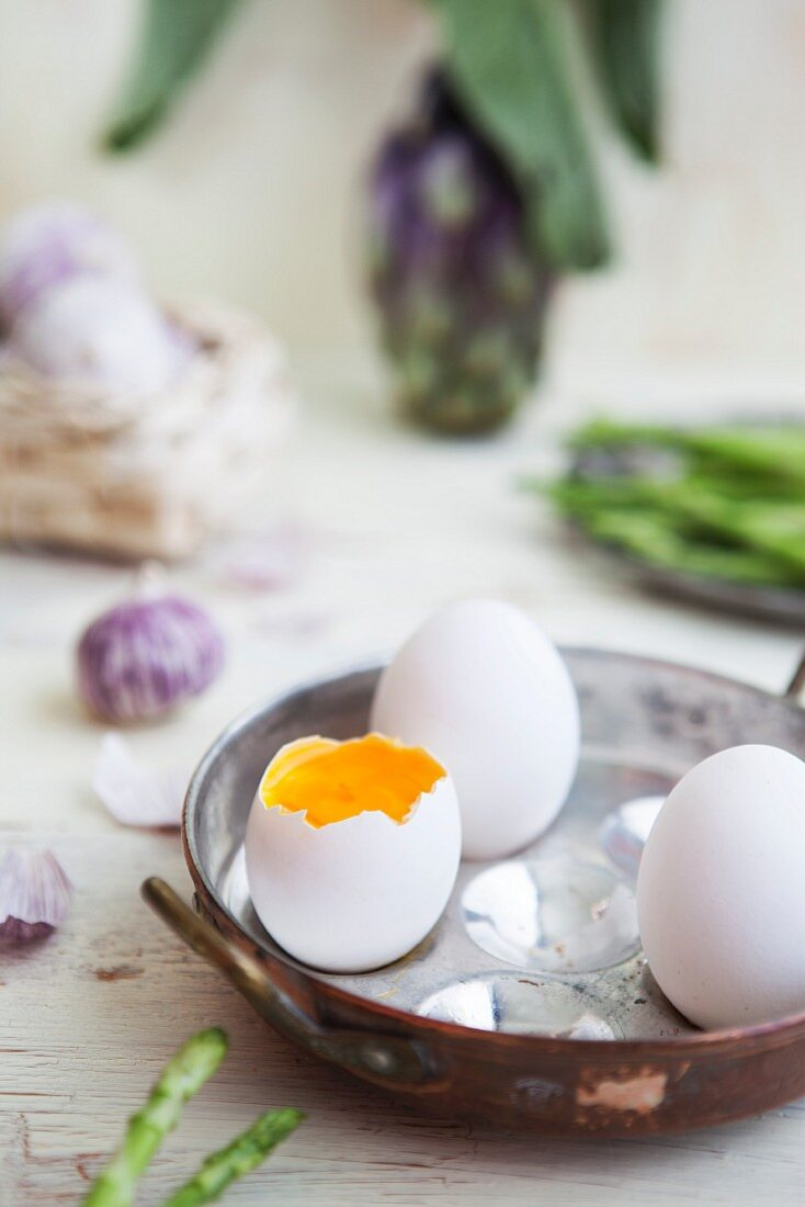 Boiled eggs in a pewter pan with asparagus, garlic and artichokes in the background