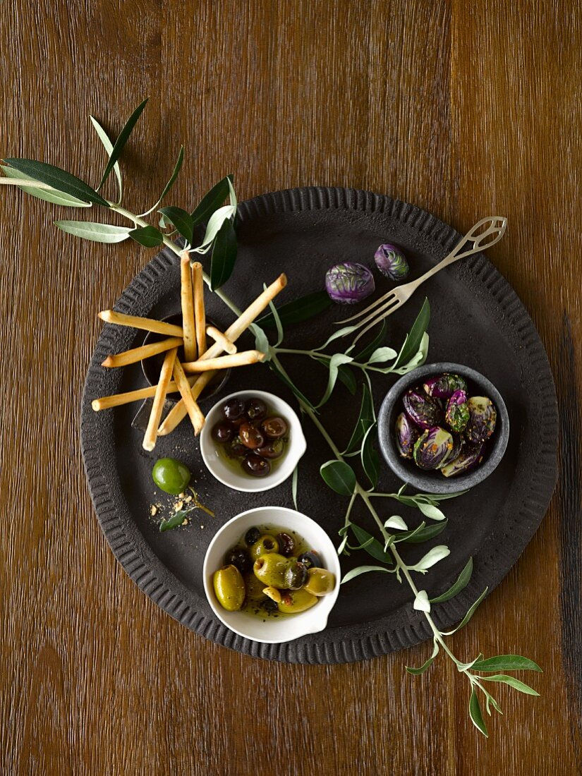 Olives, purple Brussels, bread sticks and an olive branch on a black plate
