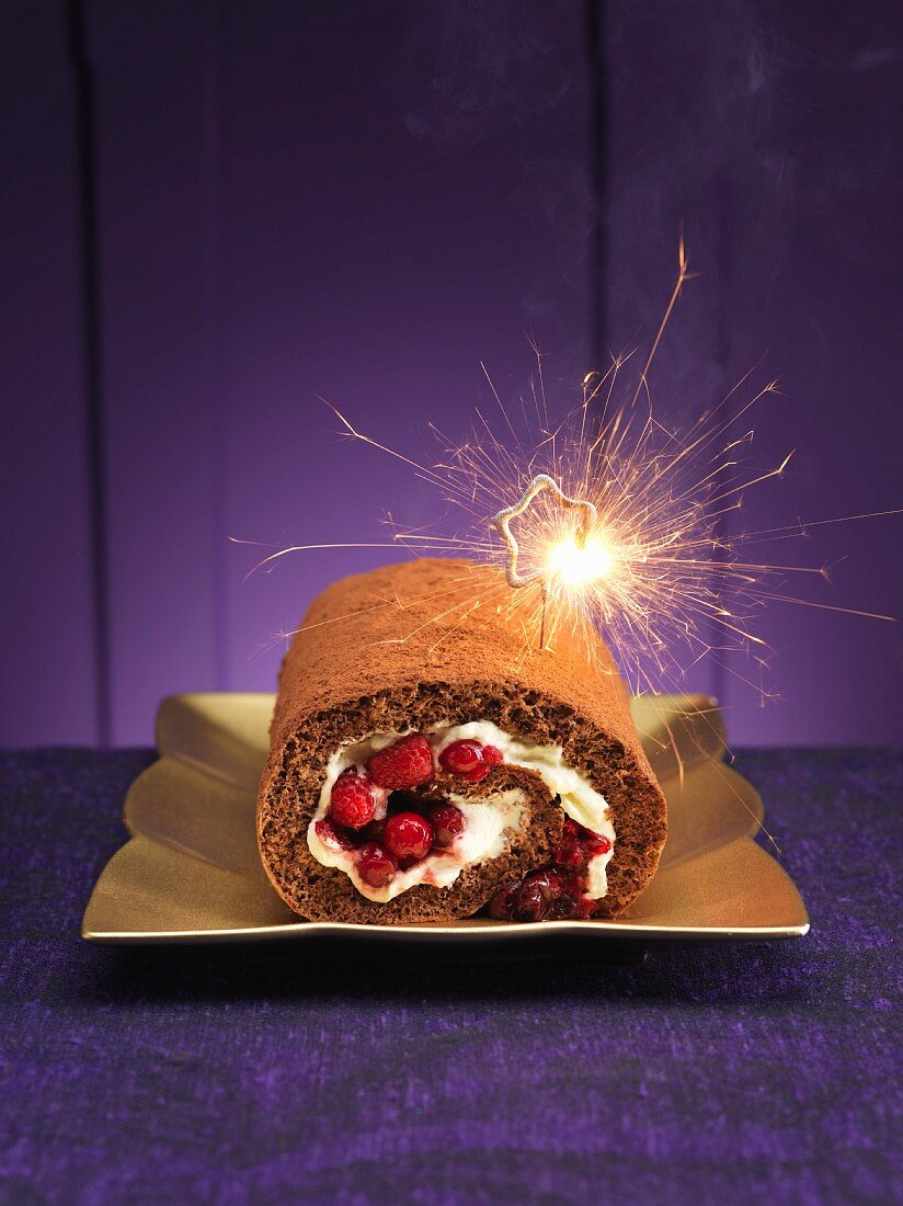 A chocolate Swiss roll with berries and a sparkler for Christmas