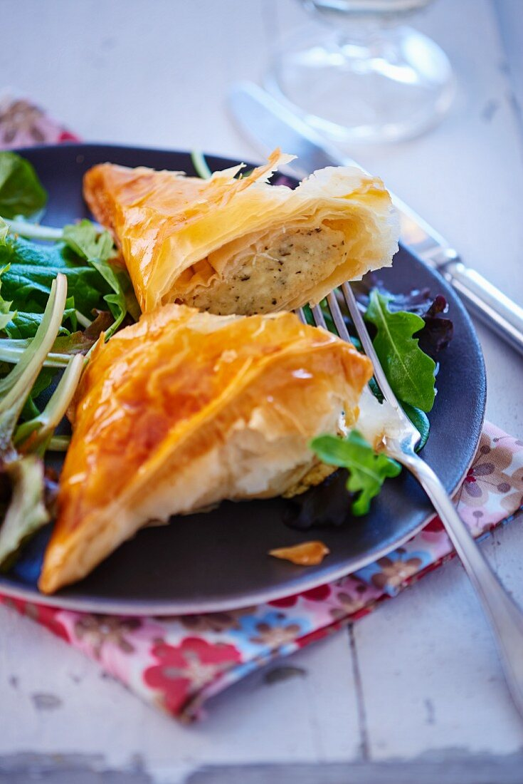A halved puff pastry parcel with a cheese filling on a rocket salad