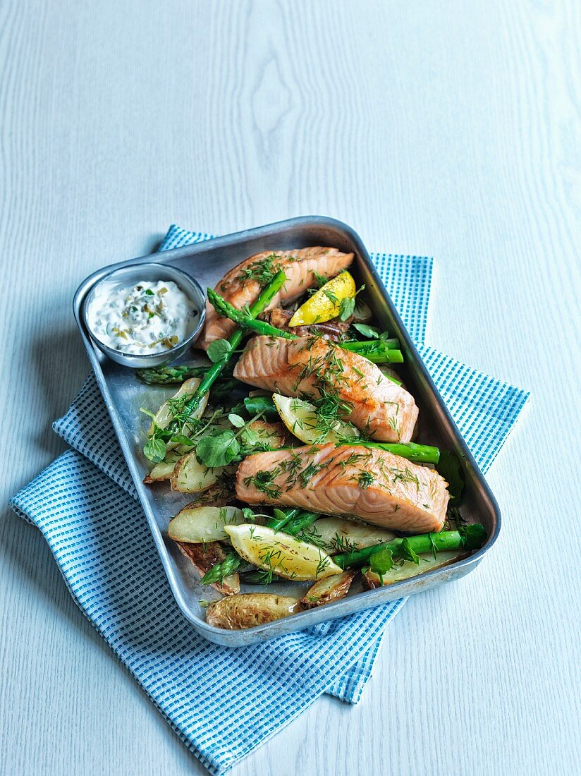 Oven roasted salmon on a bed of potatoes and green asparagus