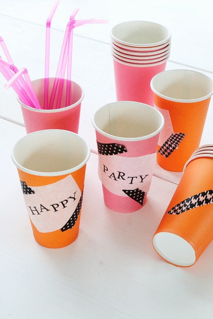 Paper cups decorated with washi tape and hand-stamped labels