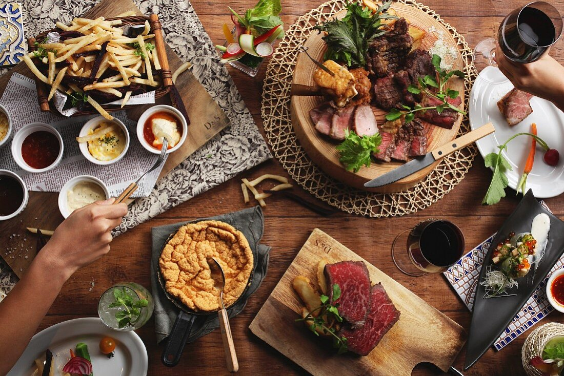 Various party dishes (chips, dips, soufflé, beef) and red wine