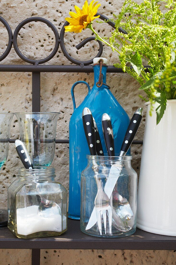 Bistro cutlery on a metal shelf against the wall of a house