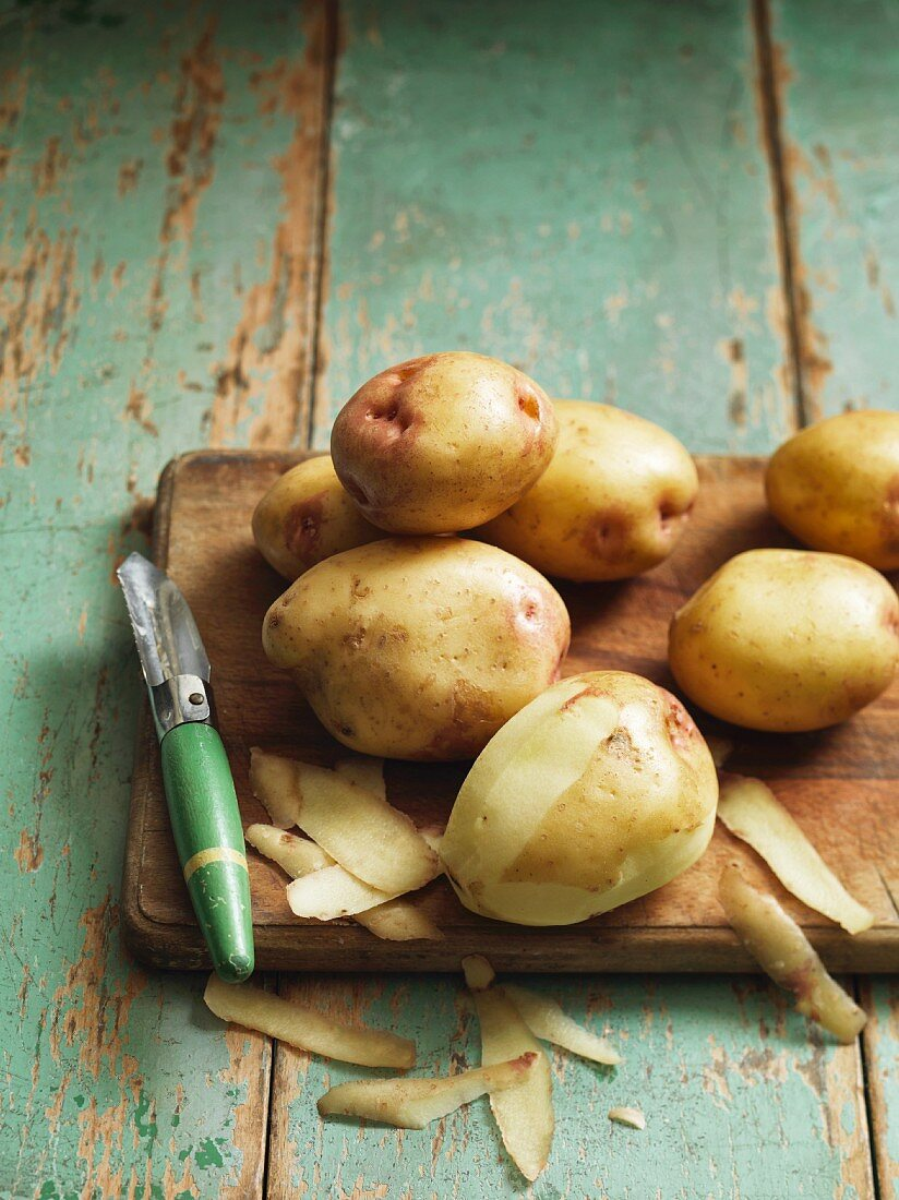 Potatoes with a peeler on a wooden board