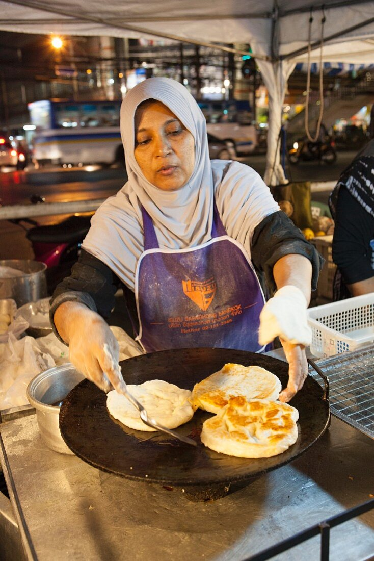 A woman frying unleavened bread at a night market in Thailand