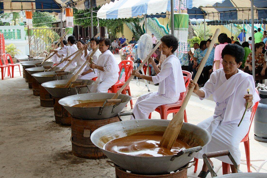 Thai women wearing white dresses preparing traditional sweet rice
