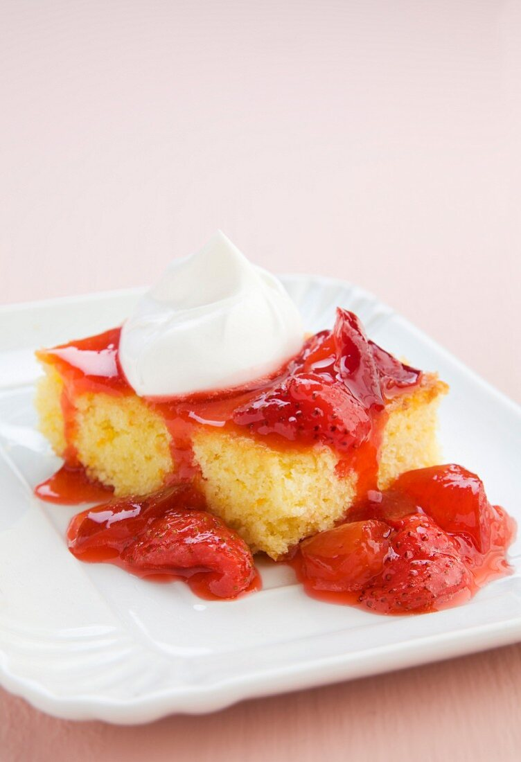 A slice of orange sponge cake with jam and a dollop of cream