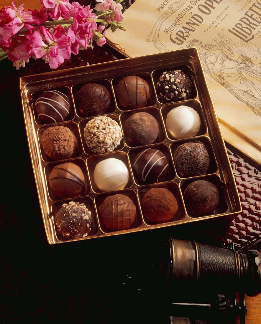 A box of truffle pralines next to a pair of opera glasses