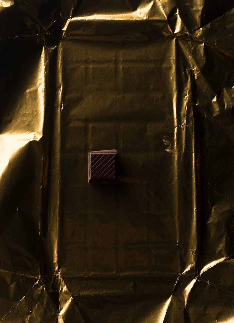 A piece of chocolate on gold paper on a table