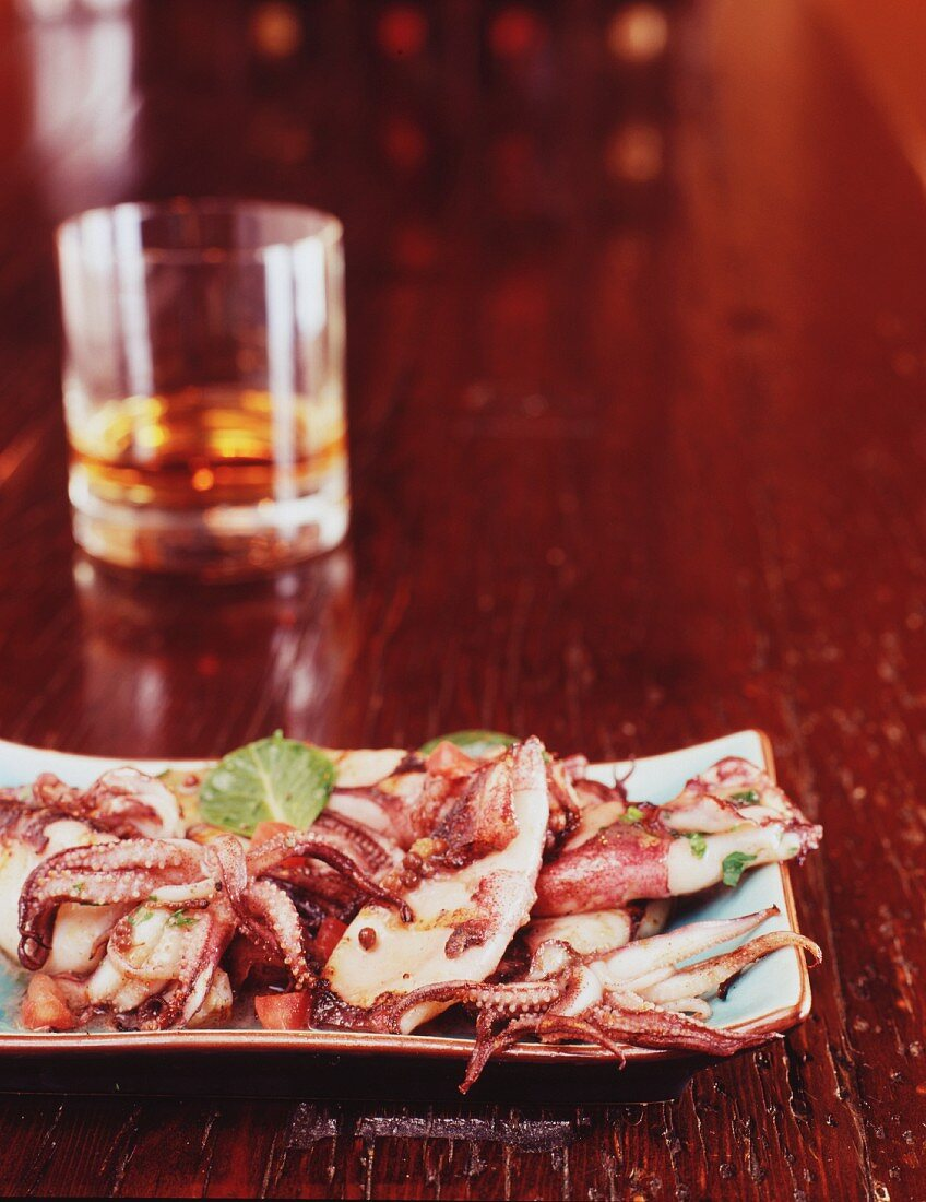 Grilled squid and a glass of single malt Scotch on a wooden bar