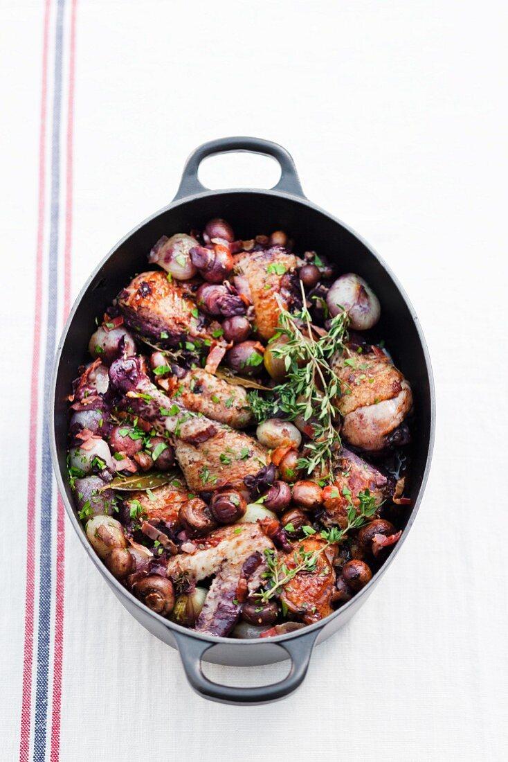 Coq au vin in a braising dish