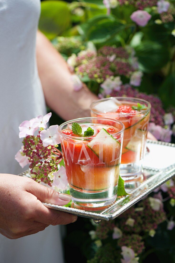 A woman carrying two glasses of refreshing fruit and cucumber drink on a tray