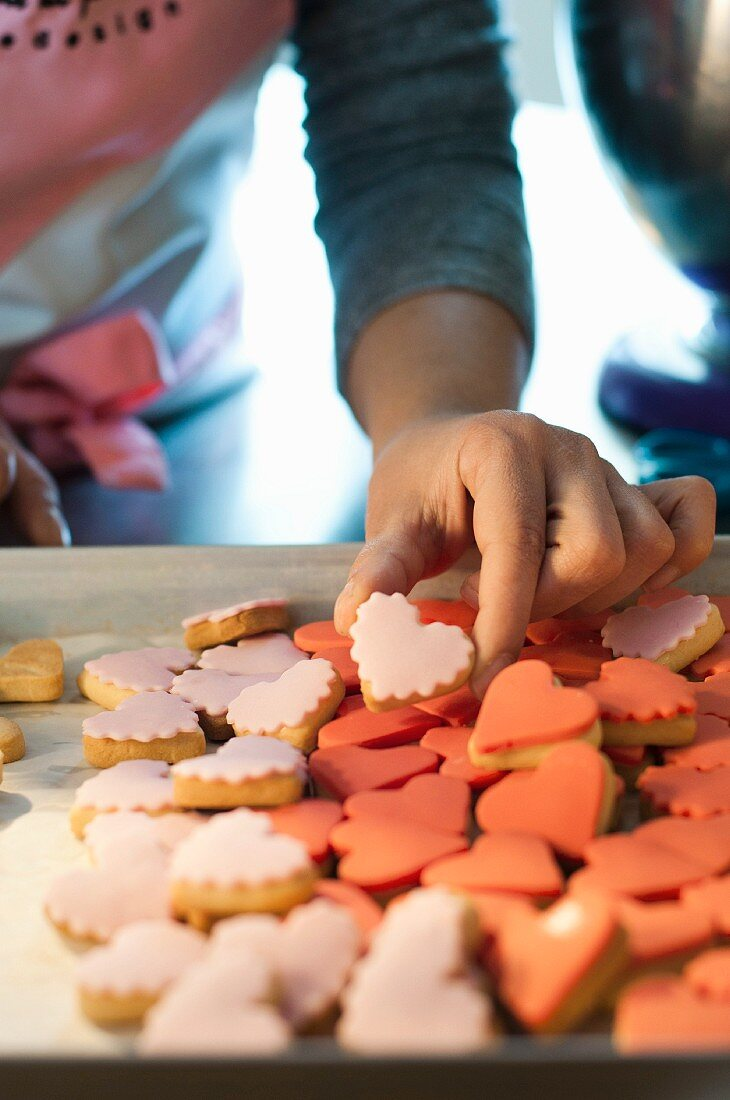 A woman holding a pink, heart-shaped biscuit