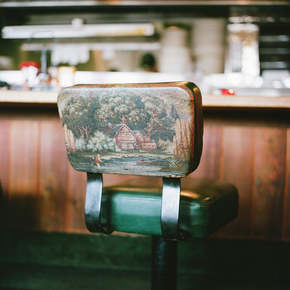 Bar stool with picture of angler in landscape on backrest