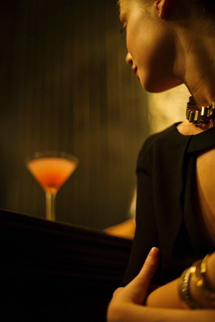 Frau sitzt mit Cocktail an der Bar