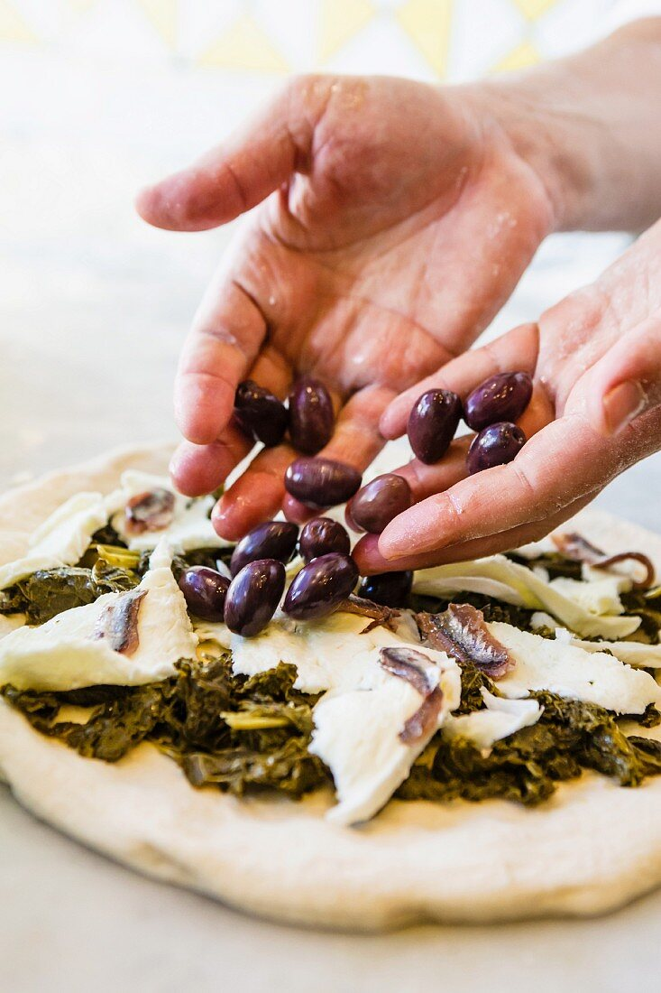 Olives being placed on a kale pizza