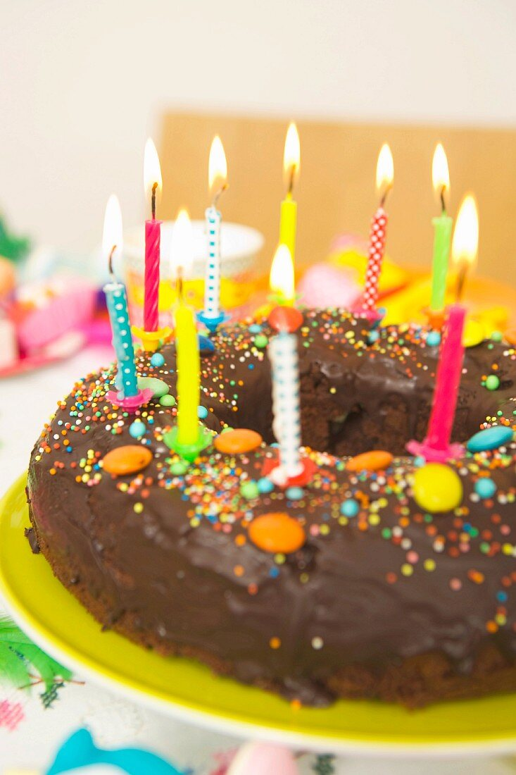 A child's birthday cake with lighted candles