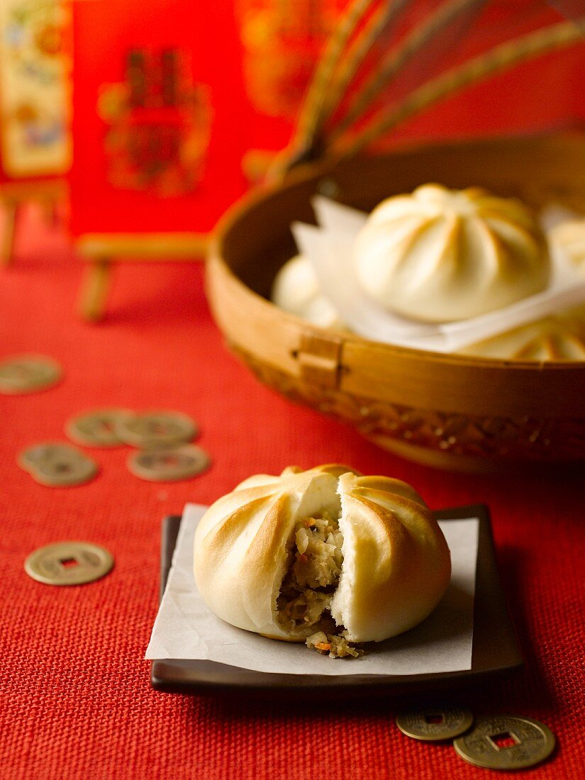 Meat filled dumplings and coins on a red tablecloth